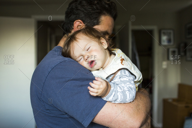 Caucasian father holding sleeping baby girl