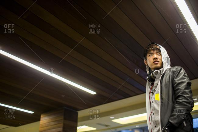 Asian man walking under wooden ceiling