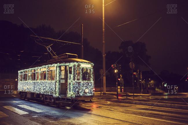 Illuminated streetcar on city street, Rome, Italy