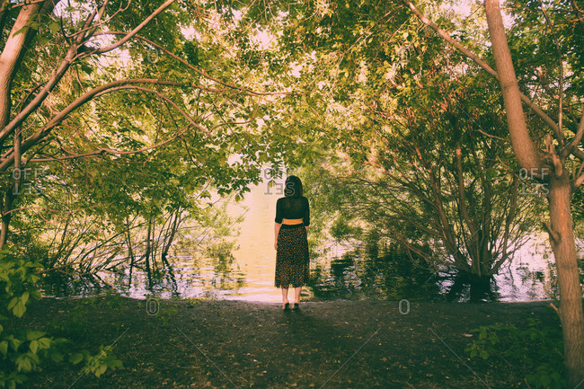 Caucasian woman standing under trees near river