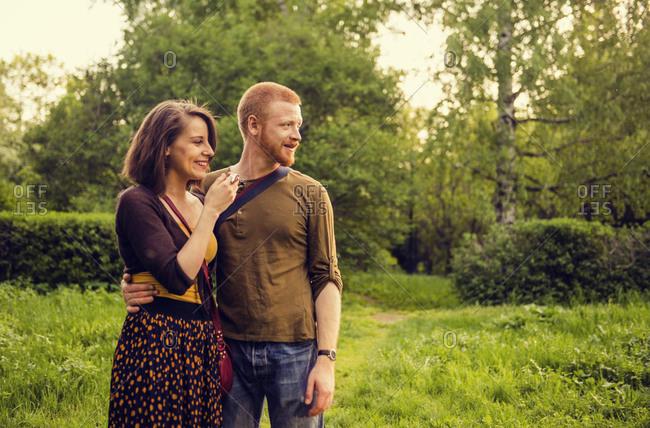 Caucasian couple hugging in field