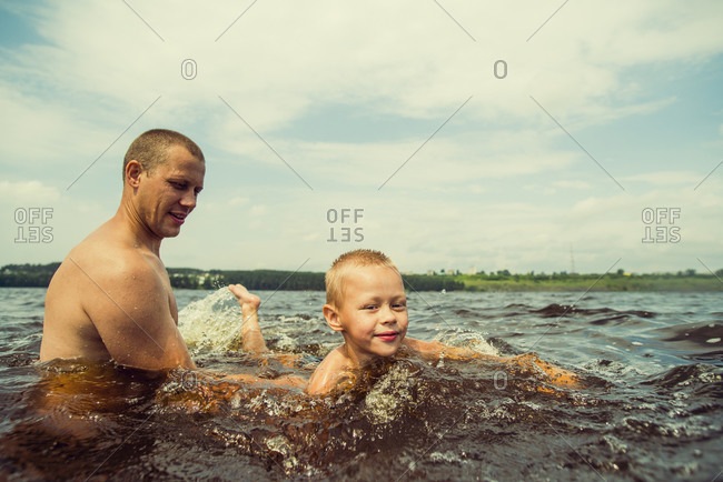 Caucasian father and son swimming in lake