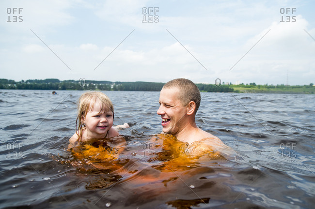 Caucasian father and daughter swimming in lake
