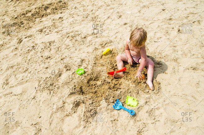 Caucasian girl playing in sand on beach