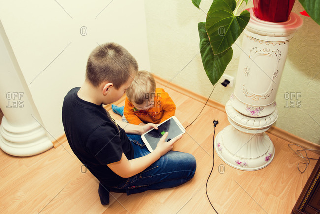 Caucasian brothers using digital tablet on floor