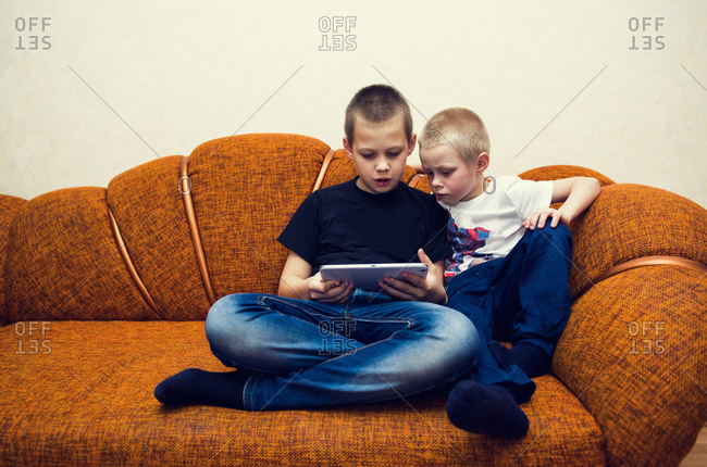 Caucasian brothers using digital tablet on sofa