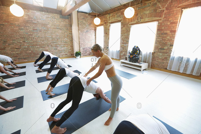 Instructor assisting student in yoga class