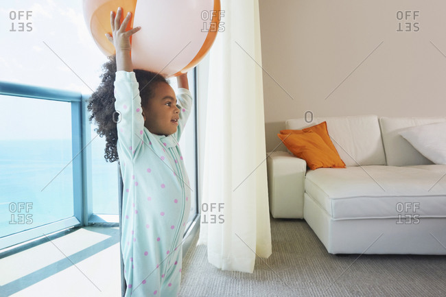 Black girl playing with beach ball in living room