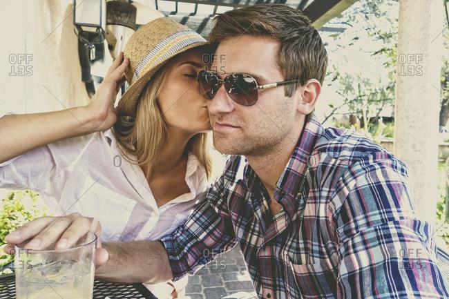 Caucasian woman kissing boyfriend at table