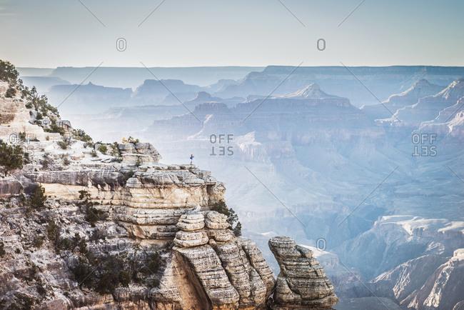 Distant Caucasian man at edge of canyon, Grand Canyon, Arizona, United States