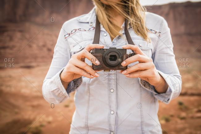 Caucasian woman photographing desert landscape