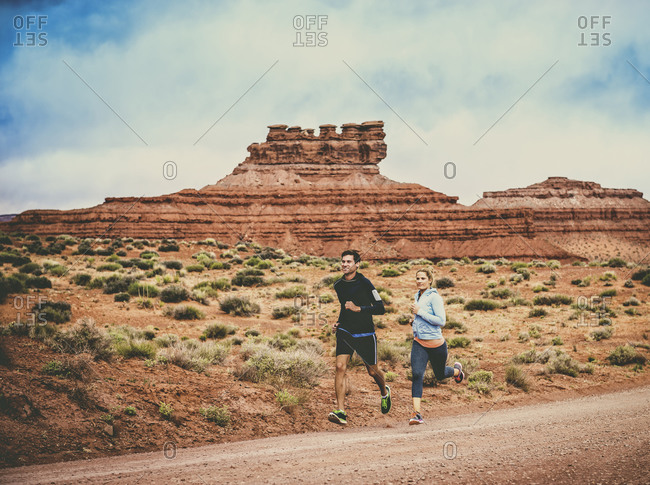 Caucasian couple running in desert landscape