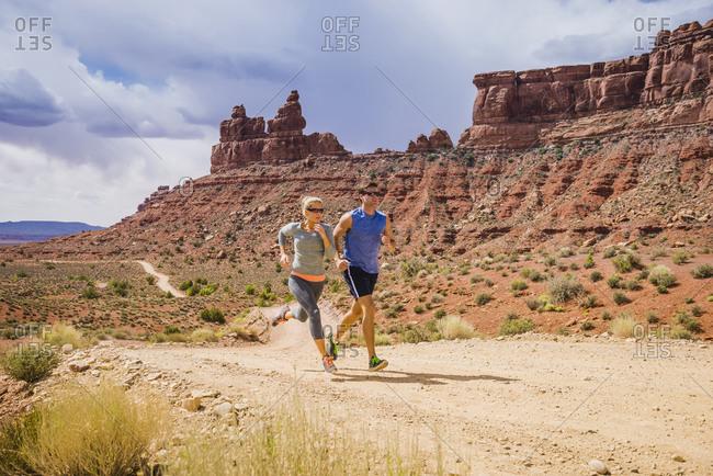Caucasian couple running in desert landscape