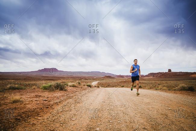 Caucasian man running in desert landscape