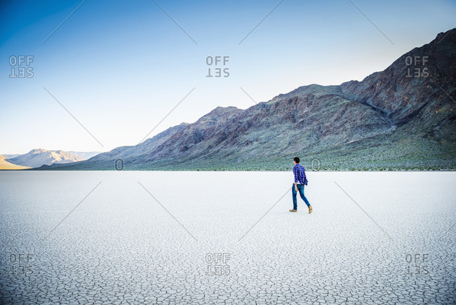Caucasian man walking in cracked desert landscape