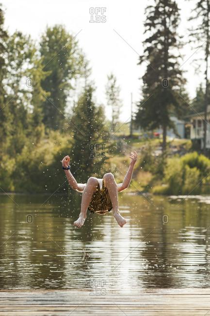 Caucasian boy jumping into lake