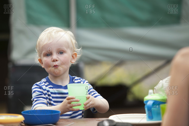 Caucasian boy eating at campsite