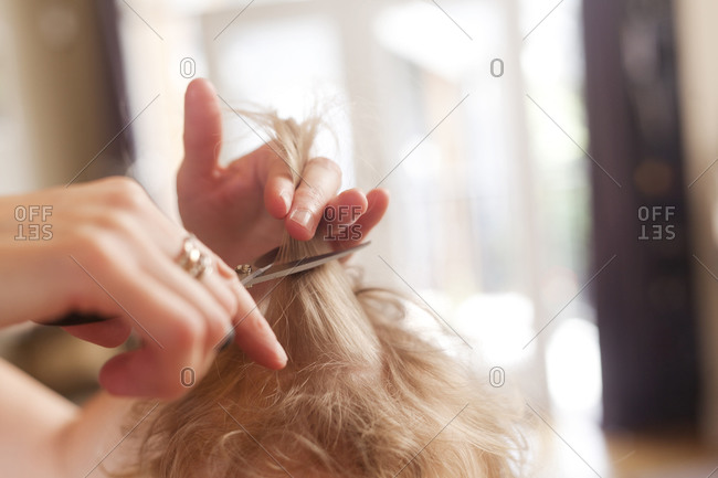 Caucasian mother cutting hair of son
