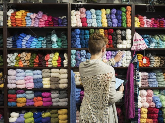 Caucasian entrepreneur taking inventory in yarn store