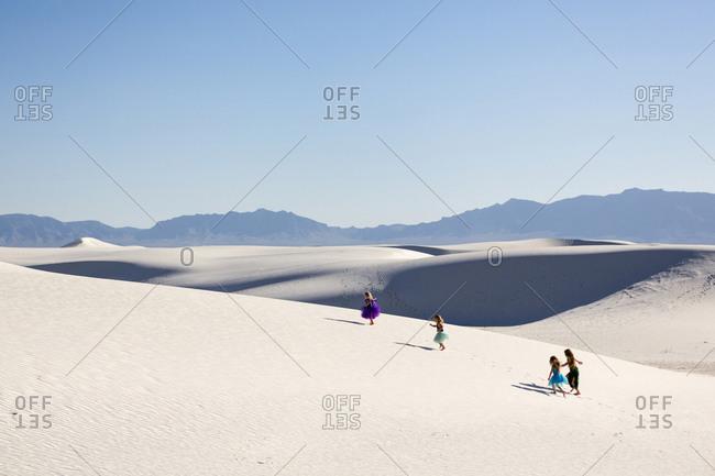 Girls walking on desert sand dunes