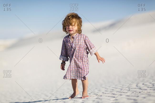 Caucasian baby boy walking on desert sand dune