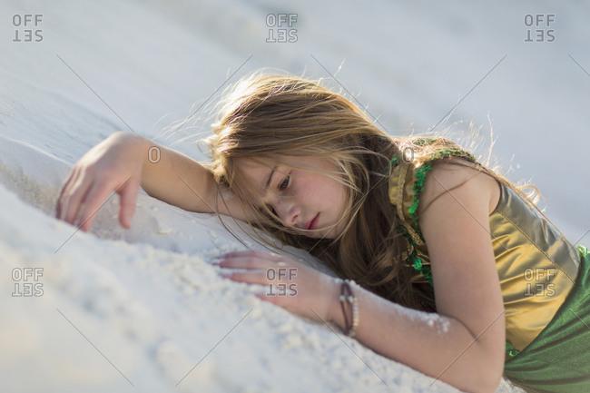 Caucasian girl laying on desert sand dune