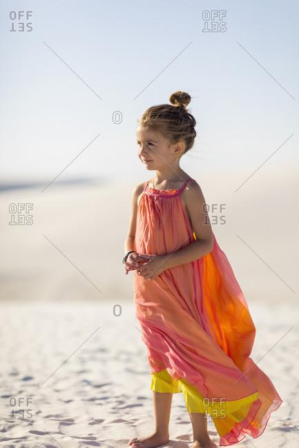 Girl standing on desert sand dune