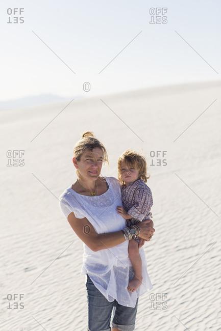 Caucasian mother holding son on desert sand dune