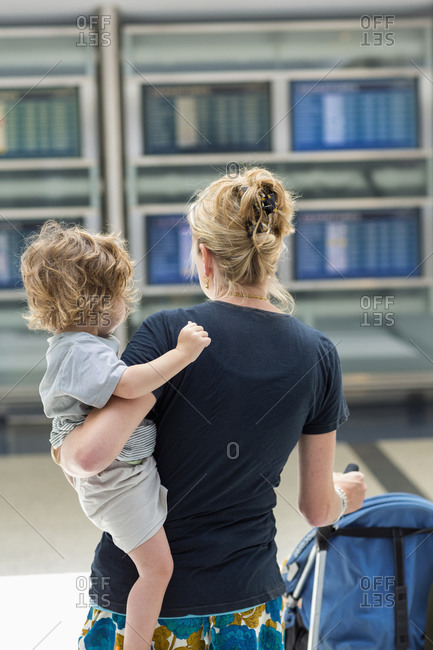 Caucasian mother carrying son in airport