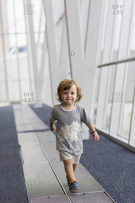 Caucasian baby boy walking in airport