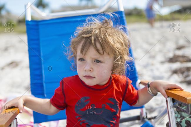 Caucasian baby boy sitting in lawn chair on beach