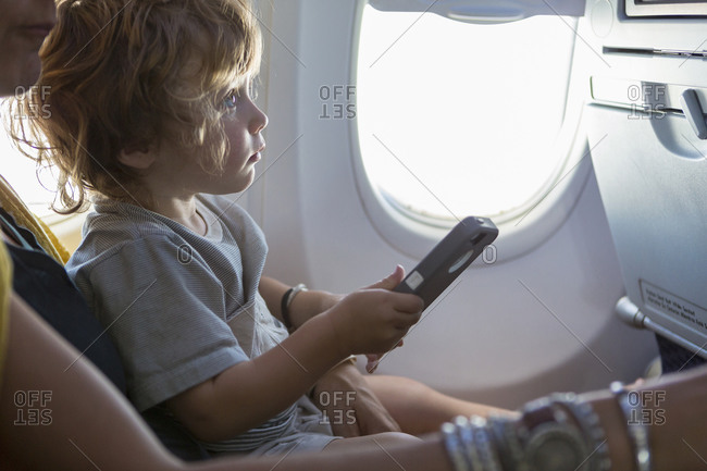 Caucasian mother and baby son using cell phone on airplane