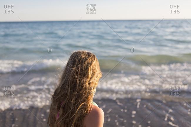 Caucasian girl watching waves on beach