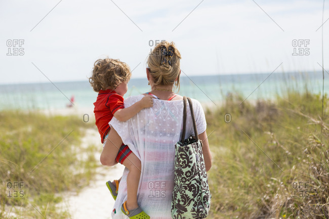 Caucasian mother carrying baby son on beach
