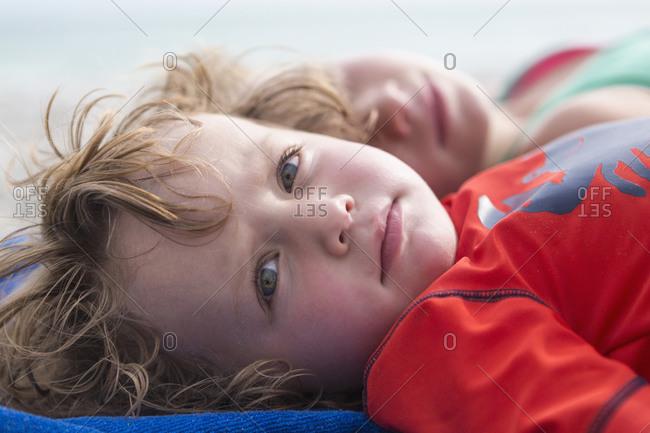 Caucasian baby boy laying on beach