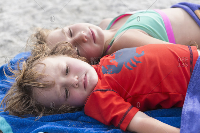 Caucasian brother and sister napping on beach