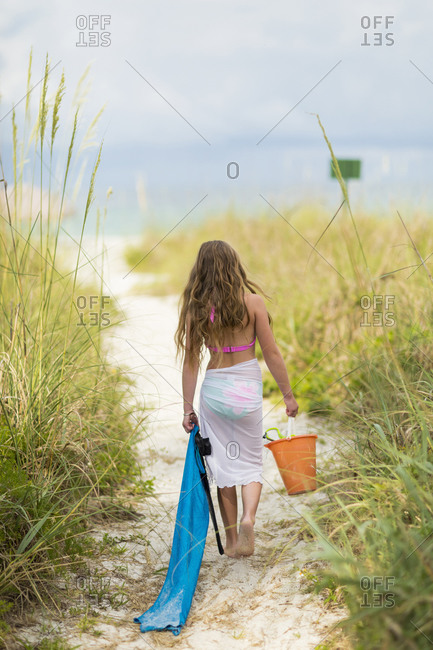 Caucasian girl carrying pail and towel on beach