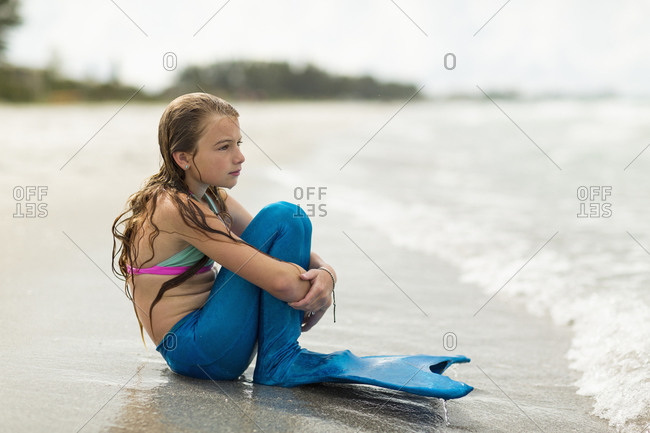 Caucasian girl wearing mermaid fin on beach