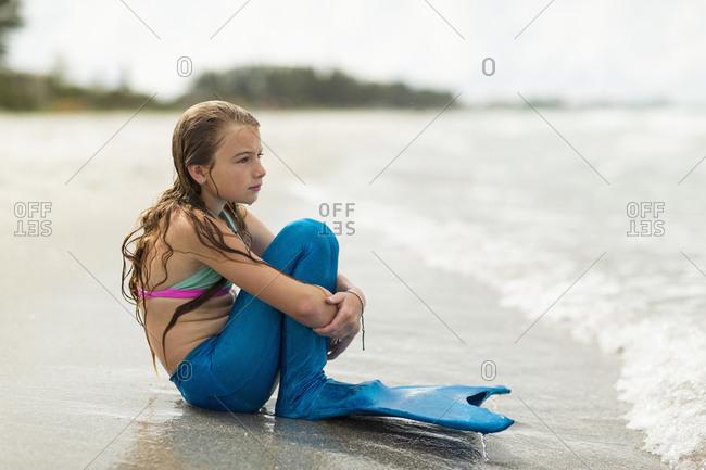 Caucasian girl wearing mermaid fin on beach