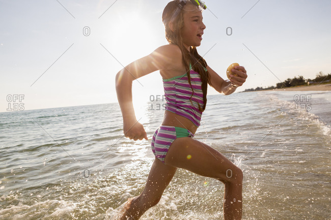 Caucasian girl running in ocean waves on beach