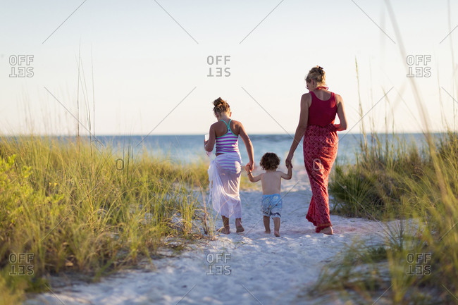 Caucasian mother and children walking on beach