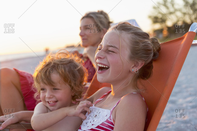 Caucasian children relaxing in lawn chair on beach