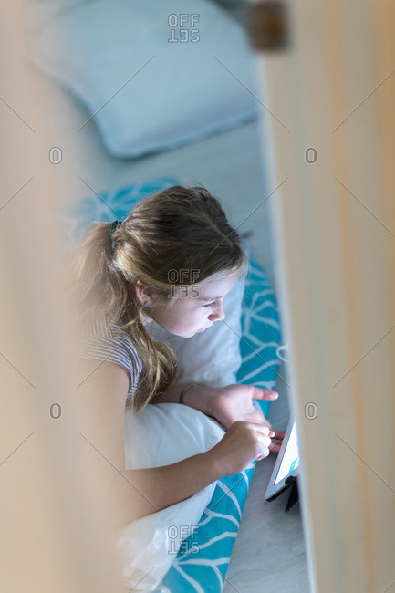 Caucasian girl using digital tablet on bed at night