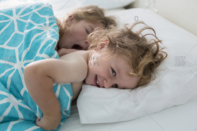 Caucasian brother and sister laying in bed