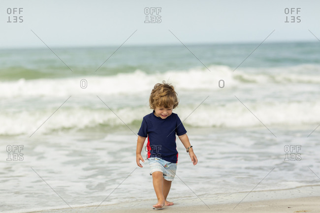 Caucasian baby boy walking on beach