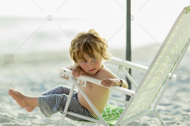 Caucasian baby boy sitting in lawn chair on beach