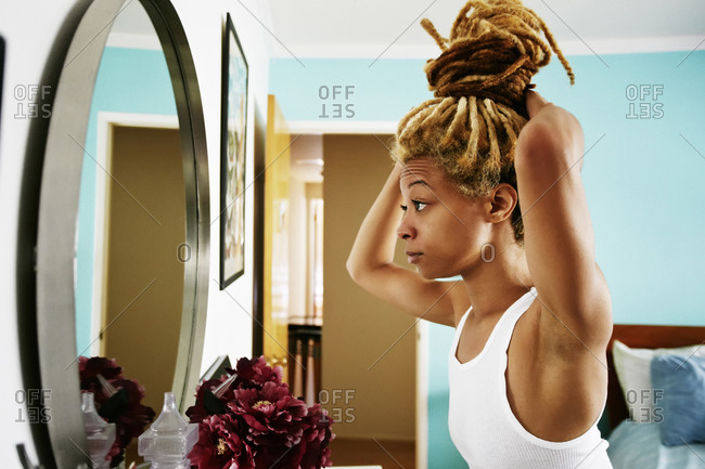 Black woman examining herself in mirror