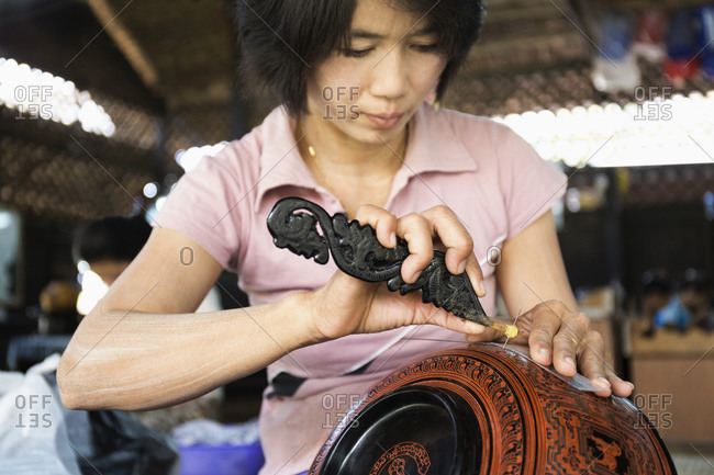 Asian artisan carving traditional design in workshop