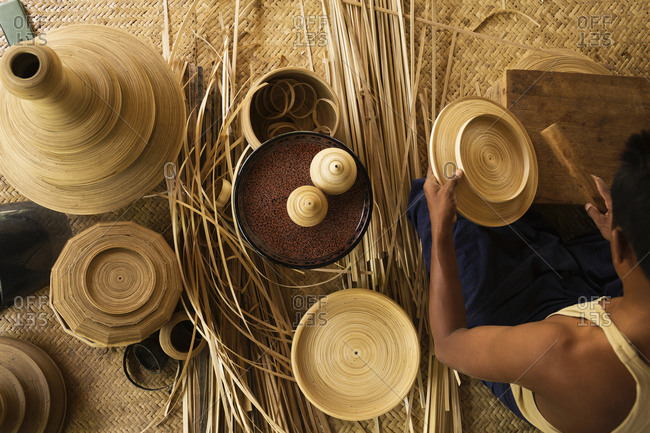 Asian artisan weaving traditional baskets in workshop