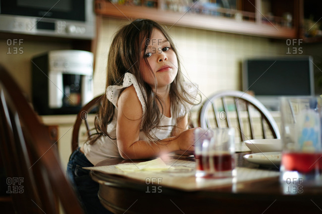 Caucasian girl eating at kitchen table